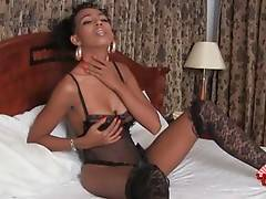 Ladyboy Da lies on bed in sexy black lingerie and stockings.